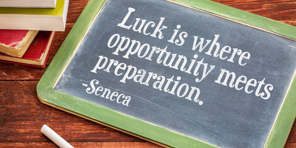 Luck is where opportunity meets preparation - Seneca quote on a slate blackboard with a white chalk and a stack of books against rustic wooden table